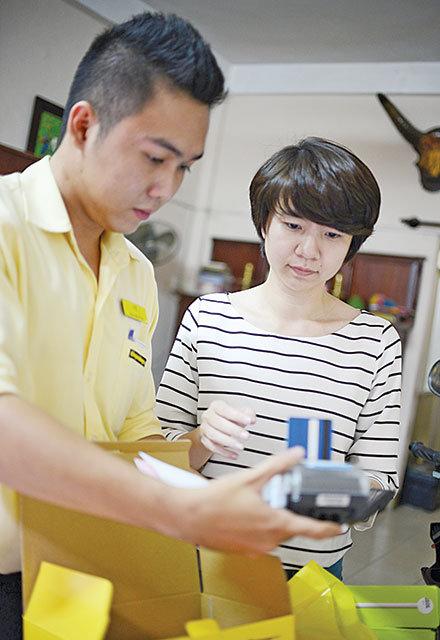 Nhân viên giao hàng và tính tiền tận nhà cho khách mua máy tính bảng qua mạng tại Q.Bình Thạnh, TP.HCM - Ảnh: T.T.D.