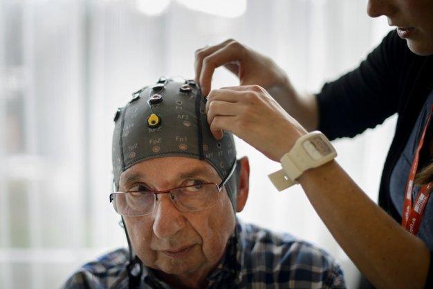 Người tham gia thử nghiệm gắn mũ điện não đồ. Ảnh AFP